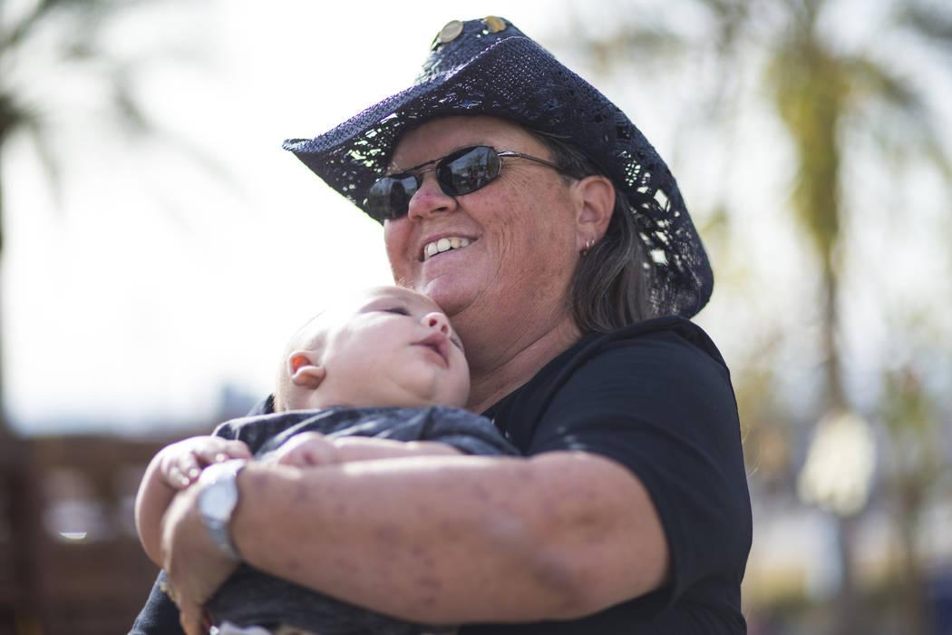 La superviviente de disparos del 1 de octubre: Sue Ann Cornwell, derecha, sostiene al infante Xander Finch cuya madre Miriam Lujan, no fotografiada, fue rescatada por Cornwell en el festival Route ...