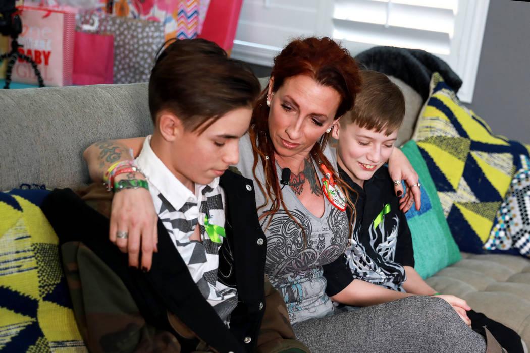 La sobreviviente del tiroteo de Las Vegas Mindy Foster, de 42 años, con sus hijos Treydon Lapetina, de 12, a su izquierda, y Trenton Lapetina, de 15, a su derecha. Foster analiza el impacto de pe ...
