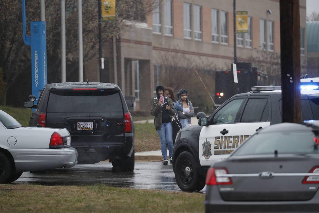 Dos estudiantes y una madre abandonan Great Mills High School, en el escenario del tiroteo, el martes 20 de marzo de 2018 en Great Mills, Maryland. El tiroteo dejó al menos tres personas heridas, ...