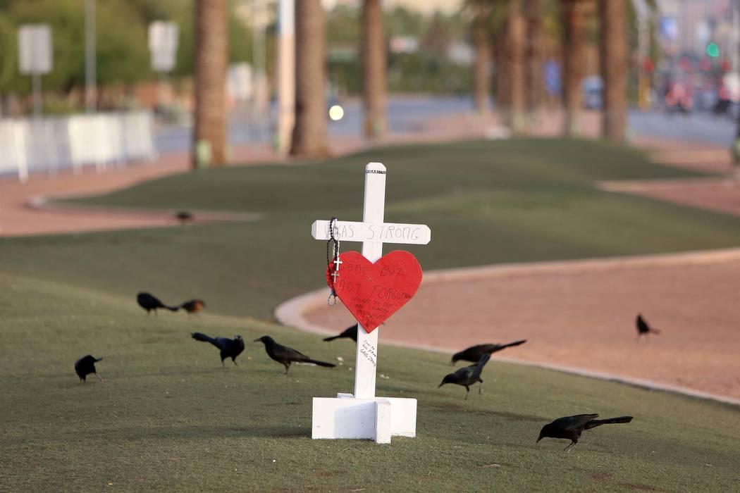 """Una cruz blanca con lema de Vegas Strong se coloca en el sitio conmemorativo del Route 91 Harvest en el letrero """"Bienvenido al Fabuloso Las Vegas"""", el lunes, 13 de octubre de 2017. (Bizuayehu Tesf ..."""