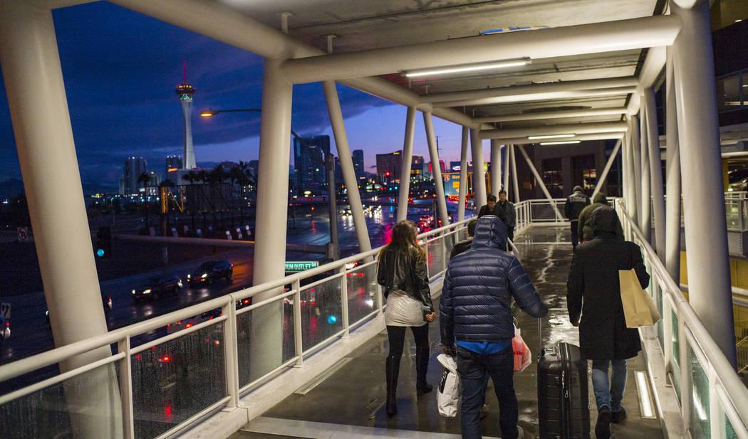 Los peatones cruzan un puente en Las Vegas North Premium Outlets cuando se pone el sol después de un largo día de lluvia en Las Vegas el martes 9 de enero de 2018. (Chase Stevens / Las Vegas Rev ...