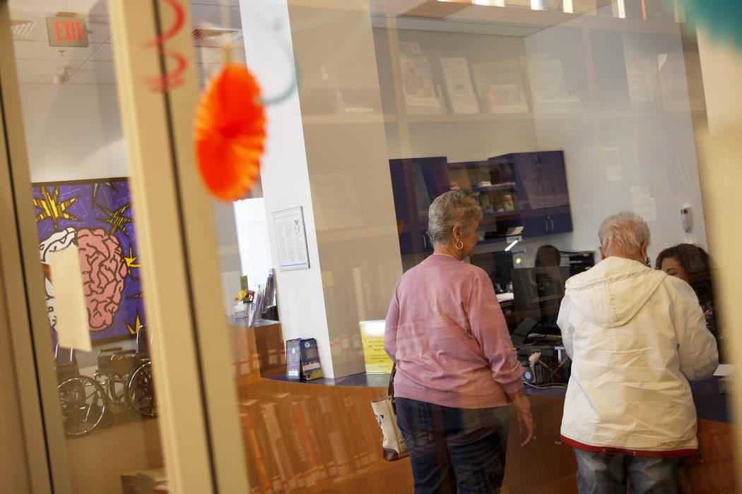 Los visitantes hablan con la recepcionista en el lobby de la Clínica Cleveland en Las Vegas, el lunes 26 de marzo de 2018. Un nuevo estudio publicado el martes por la Alzheimer's Association info ...