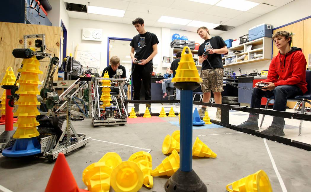 Lenny Montalbano, a la derecha, y su compañero C.D. Perkins opera su robot para apilar conos, compitiendo contra Trenton Moon, izquierda, y Matteo Cipriani durante Robot Club en la Academia Bási ...