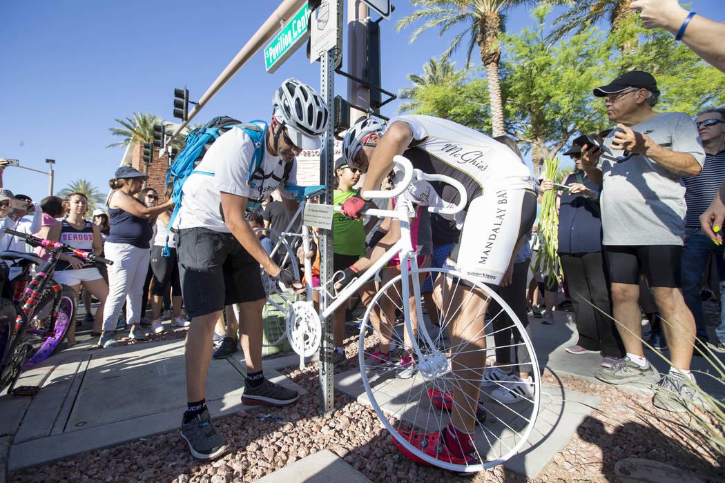 El fundador de Ghost Bikes Las Vegas Pat Treichel, izquierda, y su compañero ciclista Michael Verni armaron la bicicleta fantasma del Dr. Kayvan Khiabani durante un servicio conmemorativo en la e ...