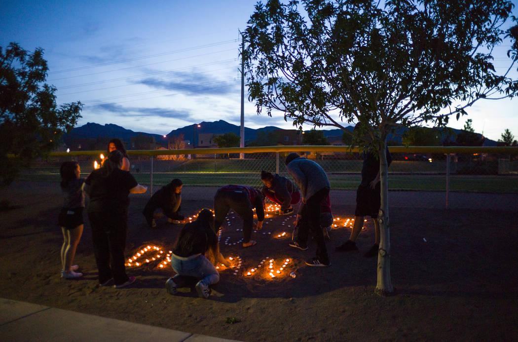 """Los asistentes colocan velas después de un velorio en Knickerbocker Park en Las Vegas el viernes 30 de marzo de 2018 para los estudiantes de Centennial High School Albert """"A.J."""" Rossi, Dylan Mack ..."""