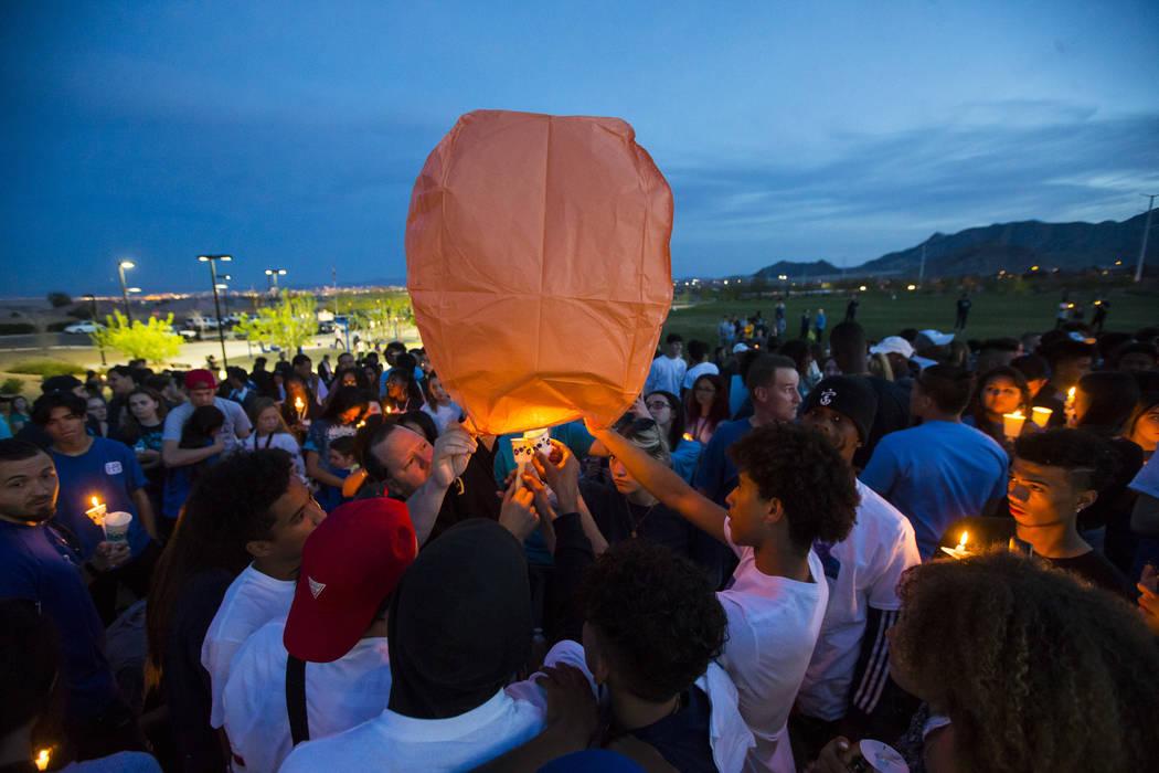 """Los asistentes encienden un globo de cantoya durante un velorio en Knickerbocker Park en Las Vegas el viernes 30 de marzo de 2018 para los estudiantes de Centennial High School Albert """"A.J."""" Rossi ..."""
