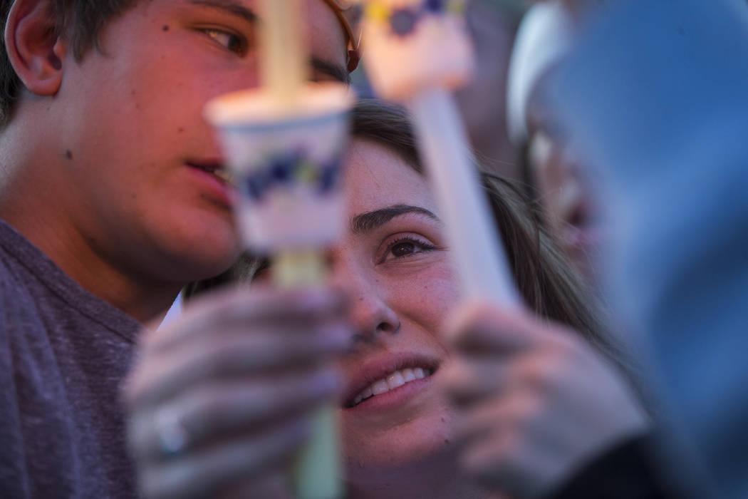 """Allie Rossi, centro, es consolada por Brennan Mecke mientras llora la pérdida de su hermano, Albert """"A.J."""" Rossi, durante un velorio a la luz de las velas en Knickerbocker Park en Las Vegas el vi ..."""