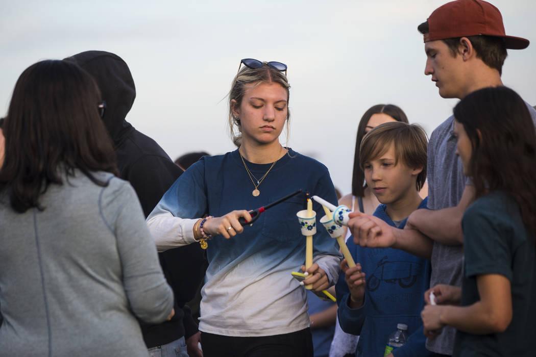Los asistentes encienden velas durante un velorio en Knickerbocker Park en Las Vegas el viernes 30 de marzo de 2018 para los estudiantes de Centennial High School Albert A.J. Rossi, Dylan Mack y B ...
