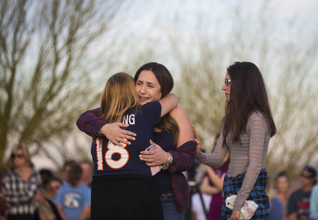 """Allie Rossi, centro, es consolada mientras llora la pérdida de su hermano, Albert """"A.J."""" Rossi, durante un velorio a la luz de las velas en Knickerbocker Park en Las Vegas el viernes 30 de marzo  ..."""