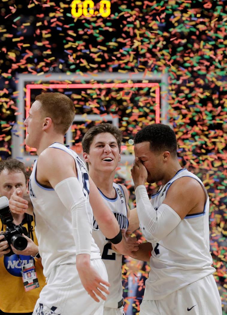 Donte DiVincenzom de Villanova se fue, Collin Gillespie y Jalen Brunson celebran después del juego de campeonato del torneo de baloncesto universitario Final Four de la NCAA contra Michigan, el l ...