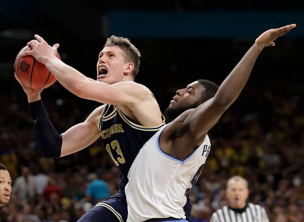 Moritz Wagner de Michigan (13) tira sobre Eric Paschall de Villanova (4) durante la segunda mitad en el juego de campeonato del torneo final de baloncesto de la universidad NCAA Final Four, el lun ...