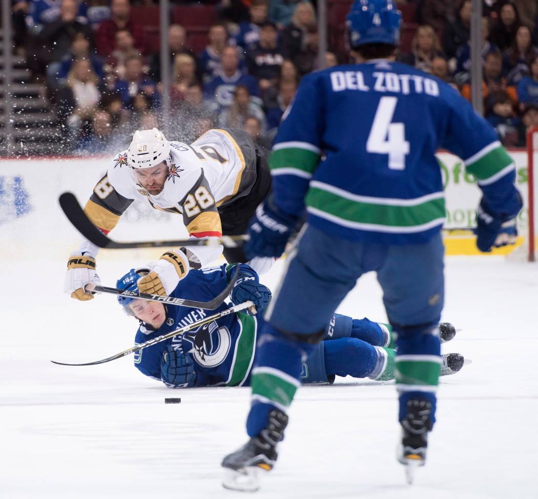 El defensor de Vancouver Canucks Michael Del Zotto (4) ve como Vegas Golden Knights dejó al extremo William Carrier (28) peleas por el control del disco con el extremo derecho Canucks Jake Virtan ...