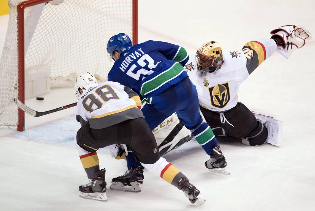 El defensor de Vegas Golden Knights Nate Schmidt (88) mira como el centro de Vancouver Canucks Bo Horvat (53) supera al portero de Golden Knights Malcolm Subban (30) durante el tercer periodo de u ...