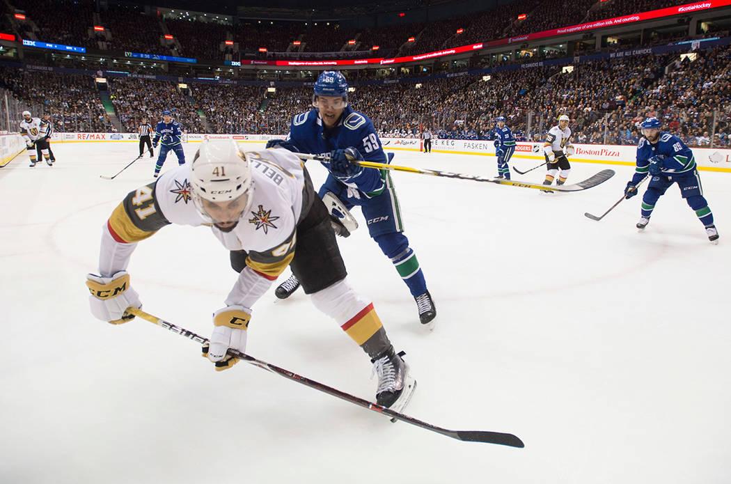 Defensor de Vancouver Canucks Ashton Sautner (59) lucha por el control del disco con el ala izquierda de Vegas Golden Knights Pierre-Edouard Bellemare (41) durante el primer periodo de un juego de ...
