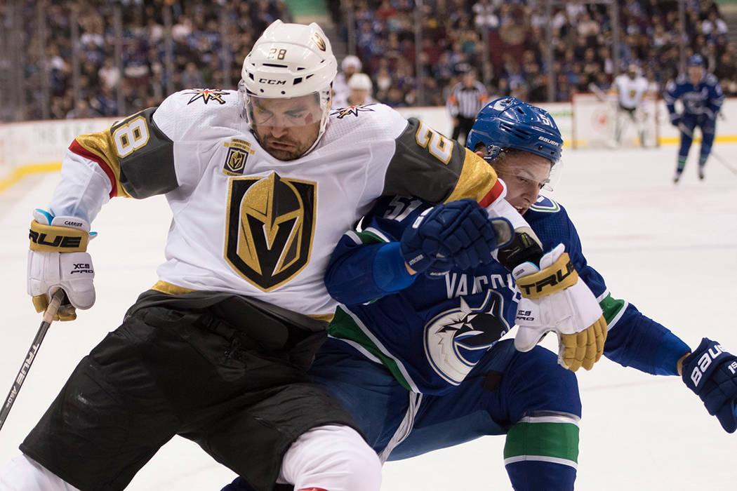 El defensa de Vancouver Canucks Troy Stecher, derecha, lucha por el control del disco con el ala izquierda de Vegas Golden Knights William Carrier (28) durante el primer periodo de un juego de hoc ...