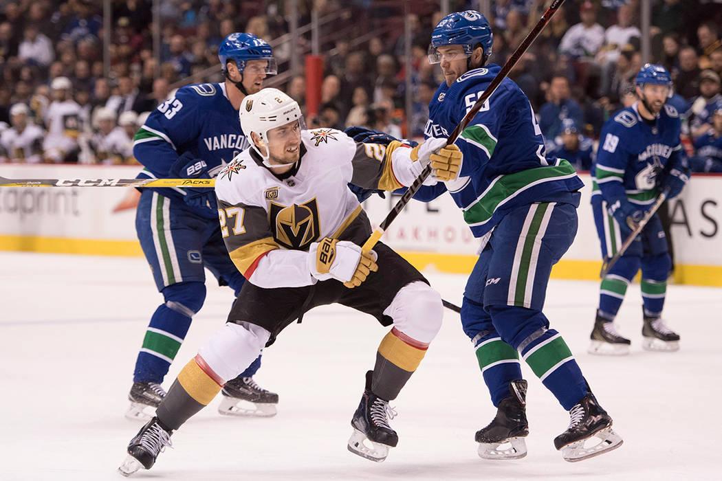 El defensor de Vegas Golden Knights Shea Theodore (27) pelea por el control del disco con el defensor de Vancouver Canucks Alex Biega durante el primer periodo de un juego de hockey de la NHL el m ...