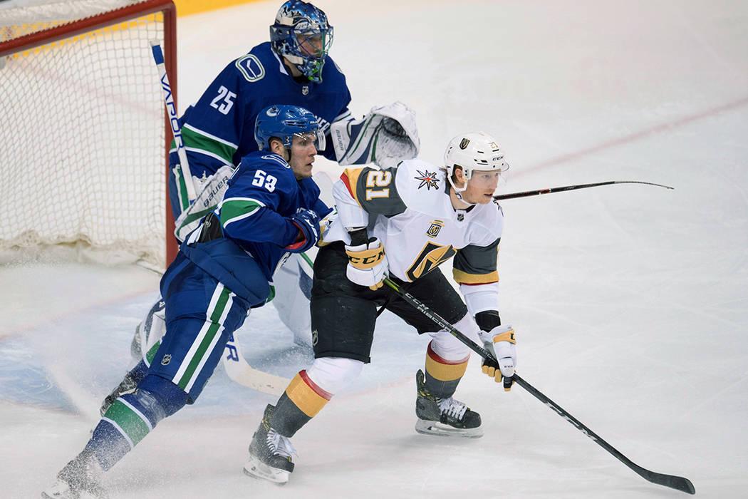 El centro de Vancouver Canucks Bo Horvat (53) intenta eliminar al centro de Vegas Golden Knights Cody Eakin (21) frente al portero de Canucks Jacob Markstrom (25) durante el segundo periodo de un  ...