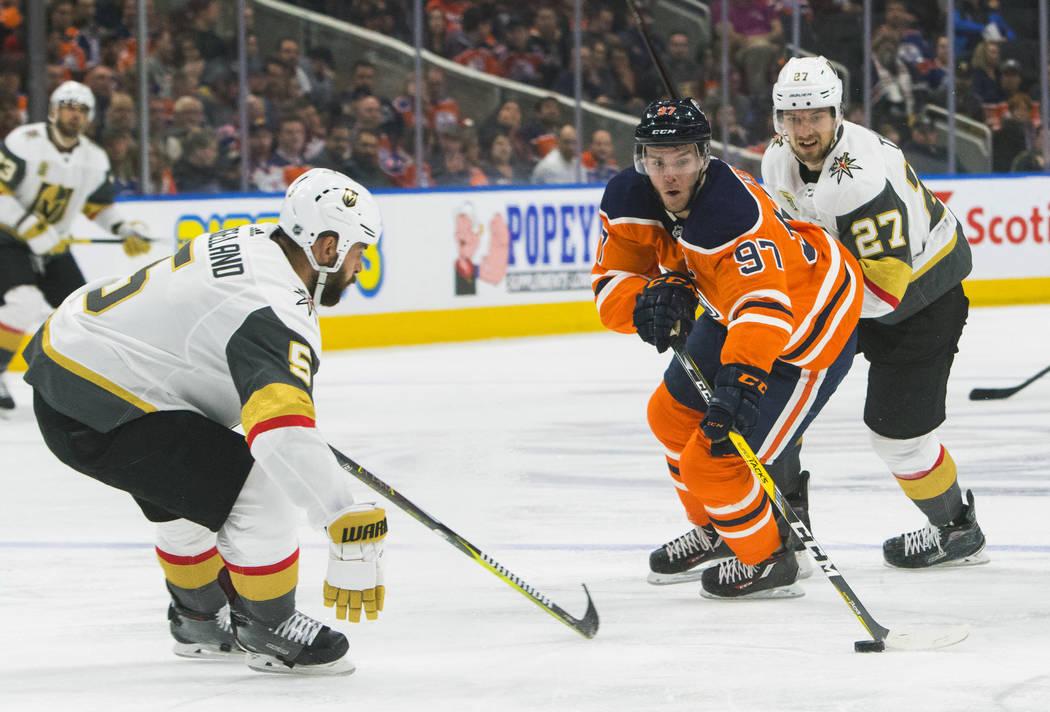 Deryk Engelland (5) de Vegas Golden Knights y su compañera de equipo Shea Theodore (27) presionan a Edmonton Oilers Connor McDavid (97) durante el segundo juego de hockey de la NHL en Edmonton, A ...