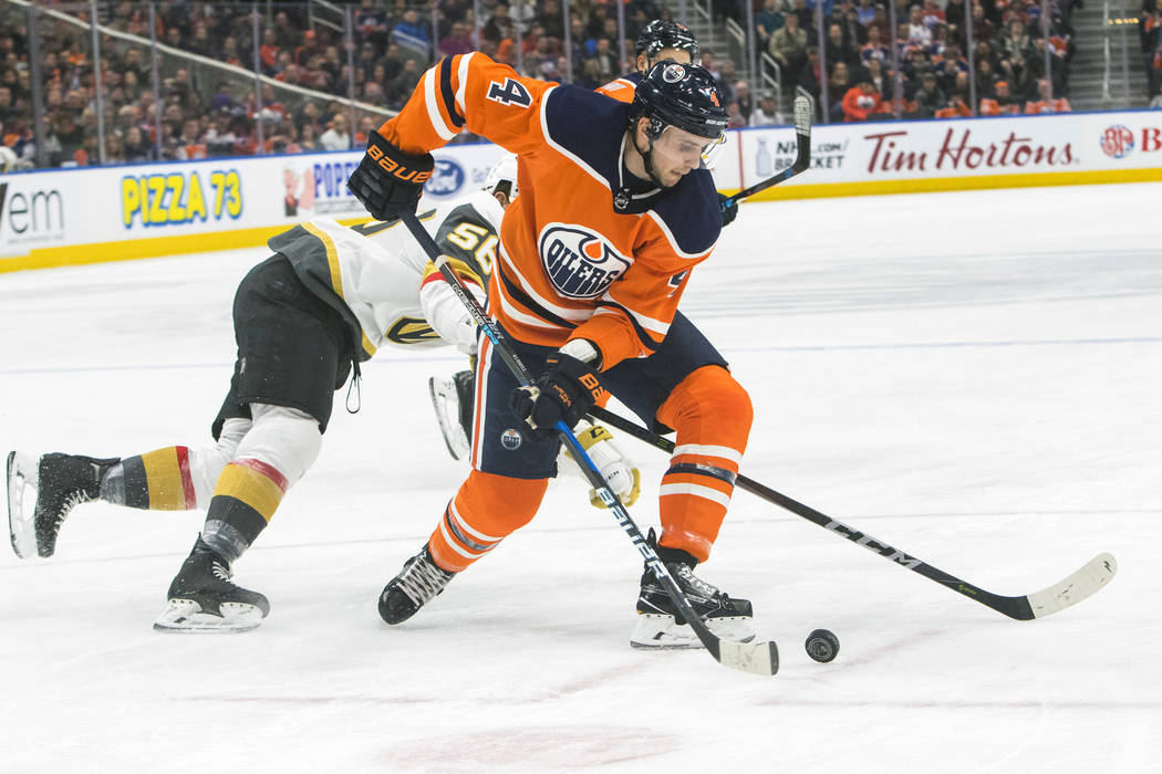 Erik Haula (56) de Vegas Golden Knights busca el disco contra Kris Russell (4) de Edmonton Oilers durante el primer juego de hockey de la NHL en Edmonton, Alberta, el jueves 5 de abril de 2018. (A ...