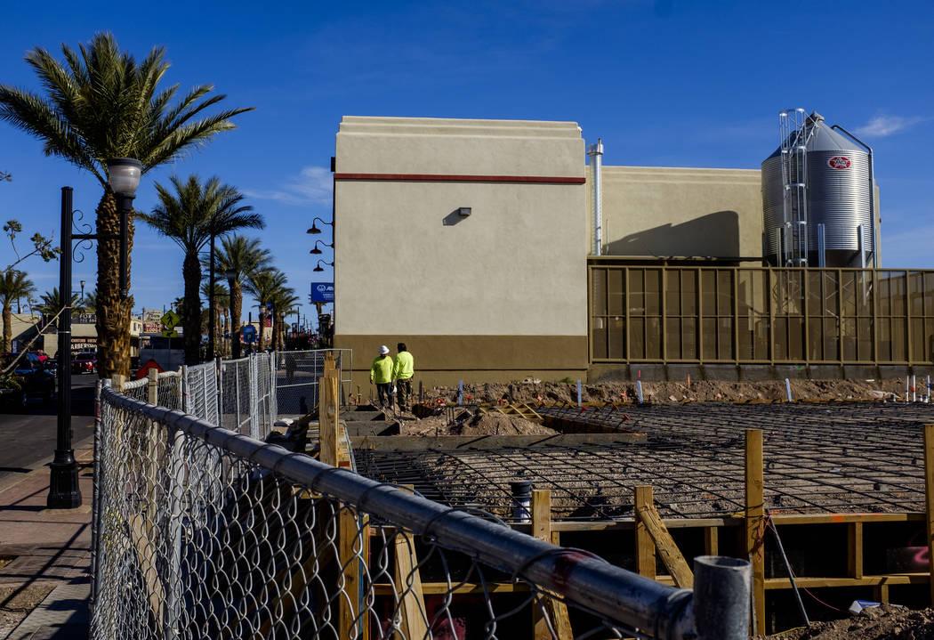 Trabajadores de la construcción en el sitio de construcción de Juan's Flaming Fajitas y Cantina con Lovelady Brewing Co. en el fondo en Water Street en Henderson el viernes 30 de marzo de 2018.  ...