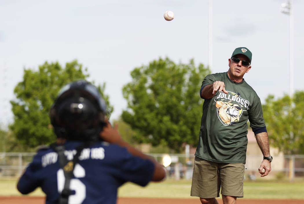 El alguacil del condado de Clark, Joe Lombardo, practica su lanzamiento con Shunta Hilliard, de 11 años, durante el Día Inaugural de la Pequeña Liga de Bolden en el Doolittle Field en Las Vegas ...