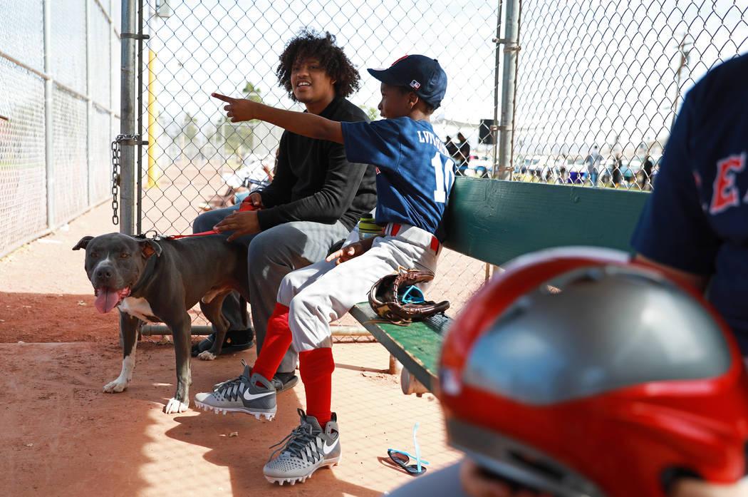 Antuan Smith y su pitbull llamado Pappa se sientan junto a Jamarion Lewis, a la derecha, durante el Día Inaugural de la Pequeña Liga de Bolden en el Doolittle Field en Las Vegas el sábado 7 de  ...