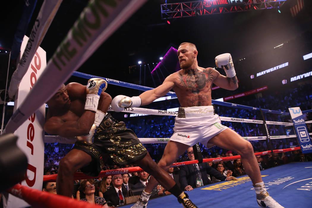 Floyd Mayweather Jr., izquierda, se inclina para evitar un golpe de Conor McGregor durante la primera ronda de su pelea en T-Mobile Arena, el sábado 26 de agosto de 2017 en Las Vegas. Benjamin Ha ...