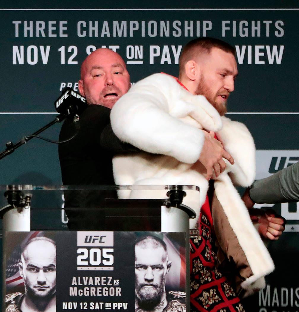 En esta foto de archivo del 10 de noviembre de 2016, el luchador Conor McGregor, a la derecha, es retenido por el presidente de la UFC Dana White durante una conferencia de prensa antes de la pele ...