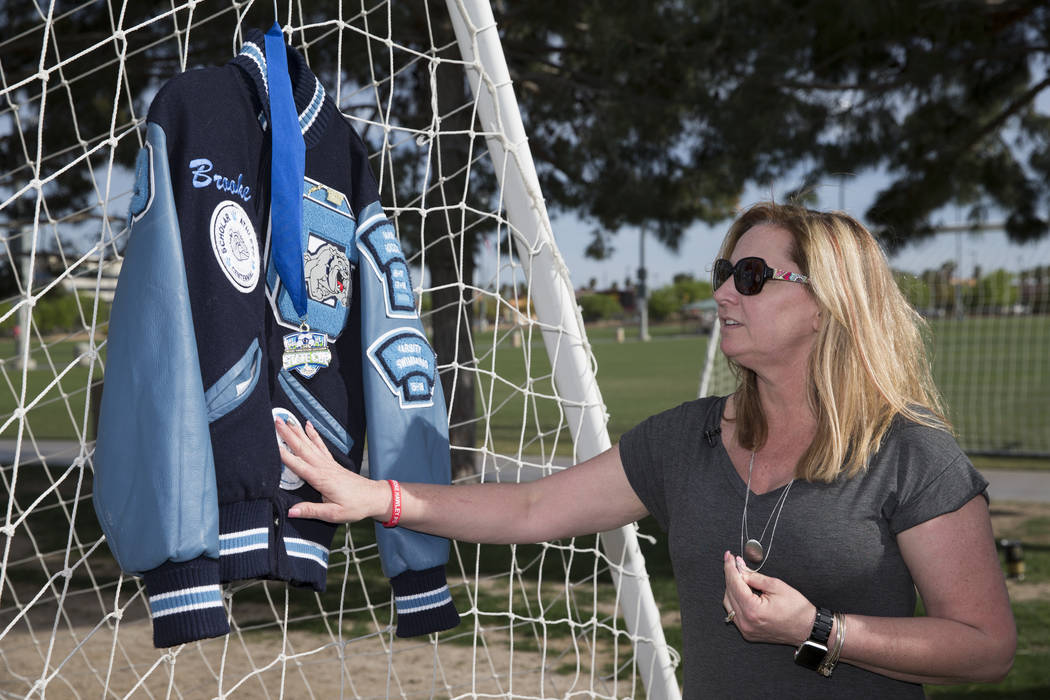 Rhonda Hawley toca la chaqueta Letterman de su hija Brooke, durante una conferencia de prensa anunciando una beca conmemorativa nombrada después de Brooke, en el Bettye Wilson Soccer Complex en L ...
