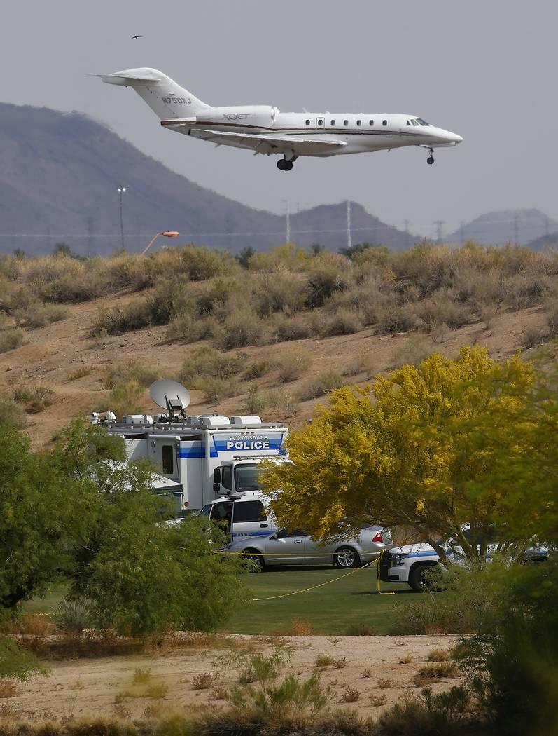 Un avión para aterrizar en el aeropuerto de Scottsdale, las autoridades se estacionan en un campo de golf cerca del sitio de un accidente aéreo que mató a varias personas el martes 10 de abril ...