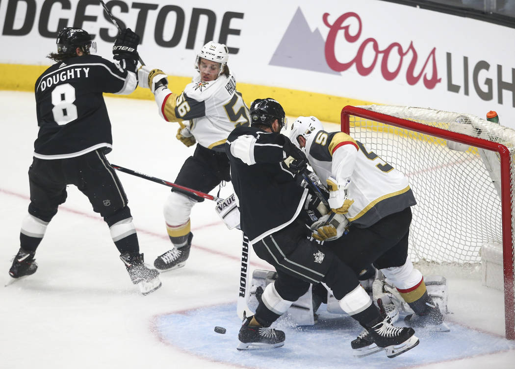 El defensor de los Golden Knights Deryk Engelland (5) y el ala izquierda Erik Haula (56) intentan marcar como defensores de Los Angeles Kings Drew Doughty (8), Jake Muzzin (6) y el portero Jonatha ...