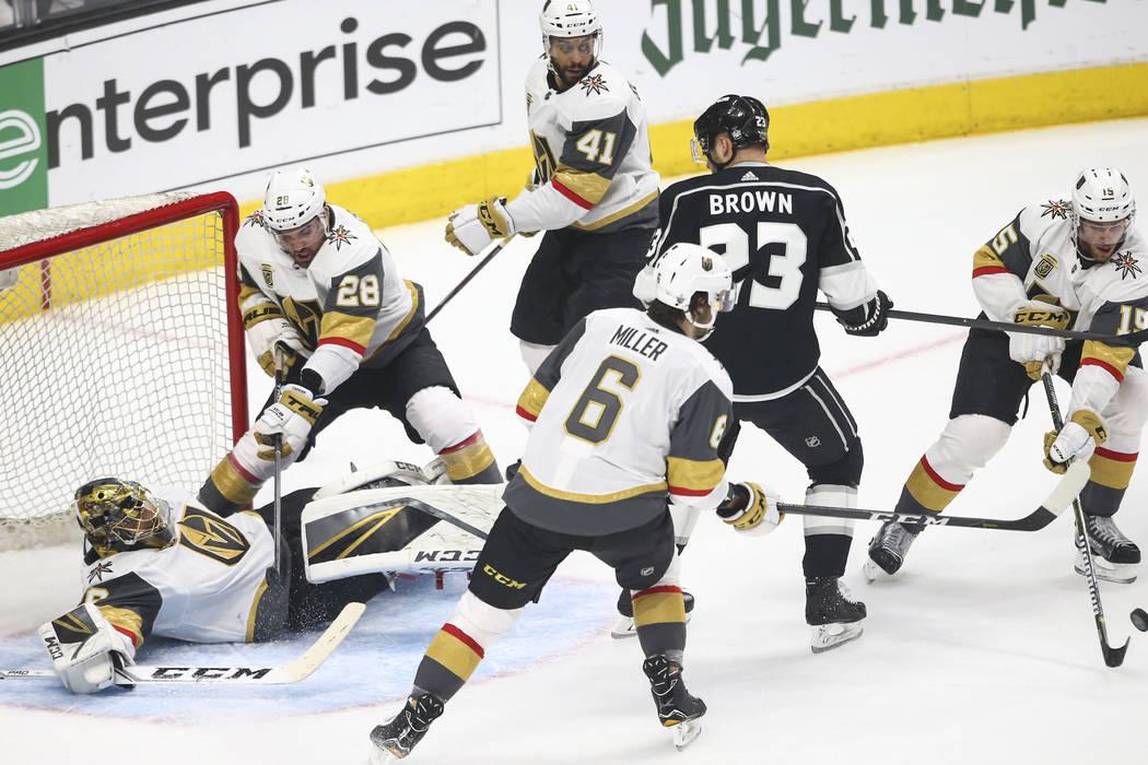 El portero de los Golden Knights: Marc-Andre Fleury (29), cae al hielo mientras el defensa Jon Merrill (15) acelera el disco mientras que el ala derecha de los Angeles Kings Dustin Brown (23) mira ...