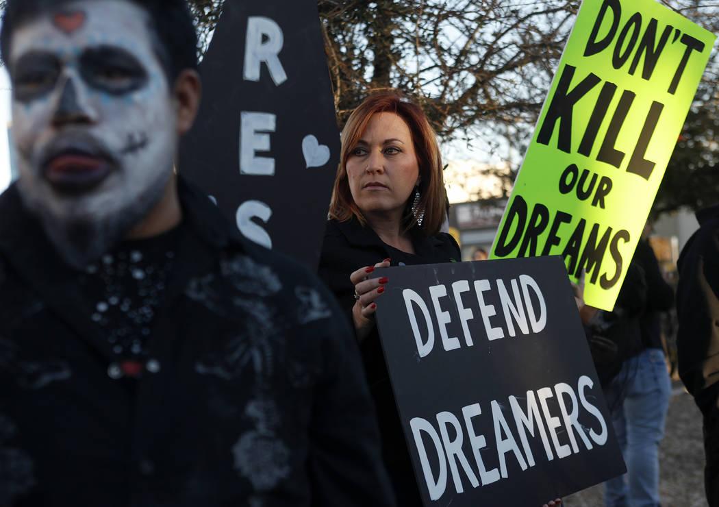 Amy Vilela, en el centro, sostiene un letrero para protestar contra el intento de la Administración Trump de terminar DACA y sus continuos cambios al programa TPS en un estacionamiento de la ofic ...