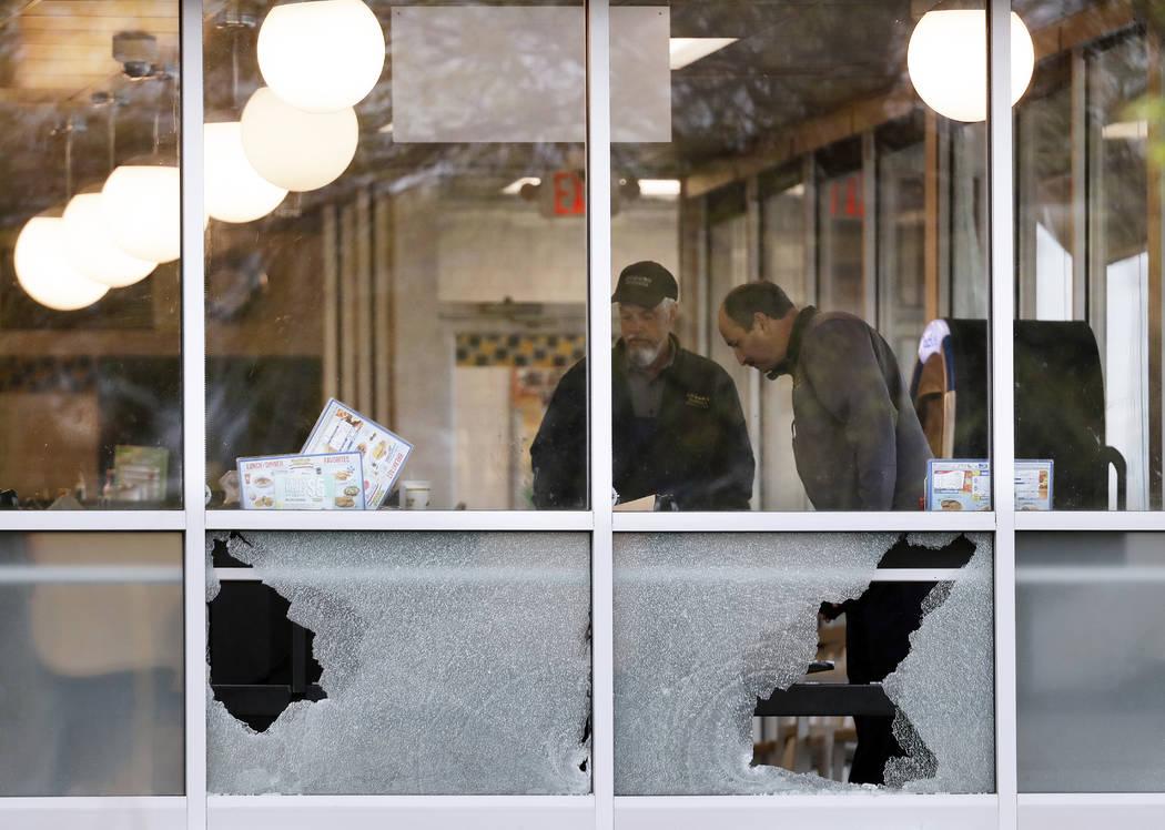La gente mira el área cerca de una ventana que fue disparada en un restaurante de una Waffle House el domingo 22 de abril de 2018 en Nashville, Tenn. Al menos cuatro personas murieron después de ...