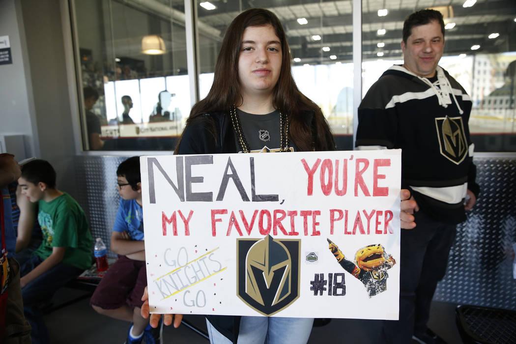 Gia Avalone, de 14 años, con su padre Steven mirando, muestra su póster mientras esperaban entrar en la zona infantil durante una práctica de Vegas Golden Knights en City National Arena en Las ...