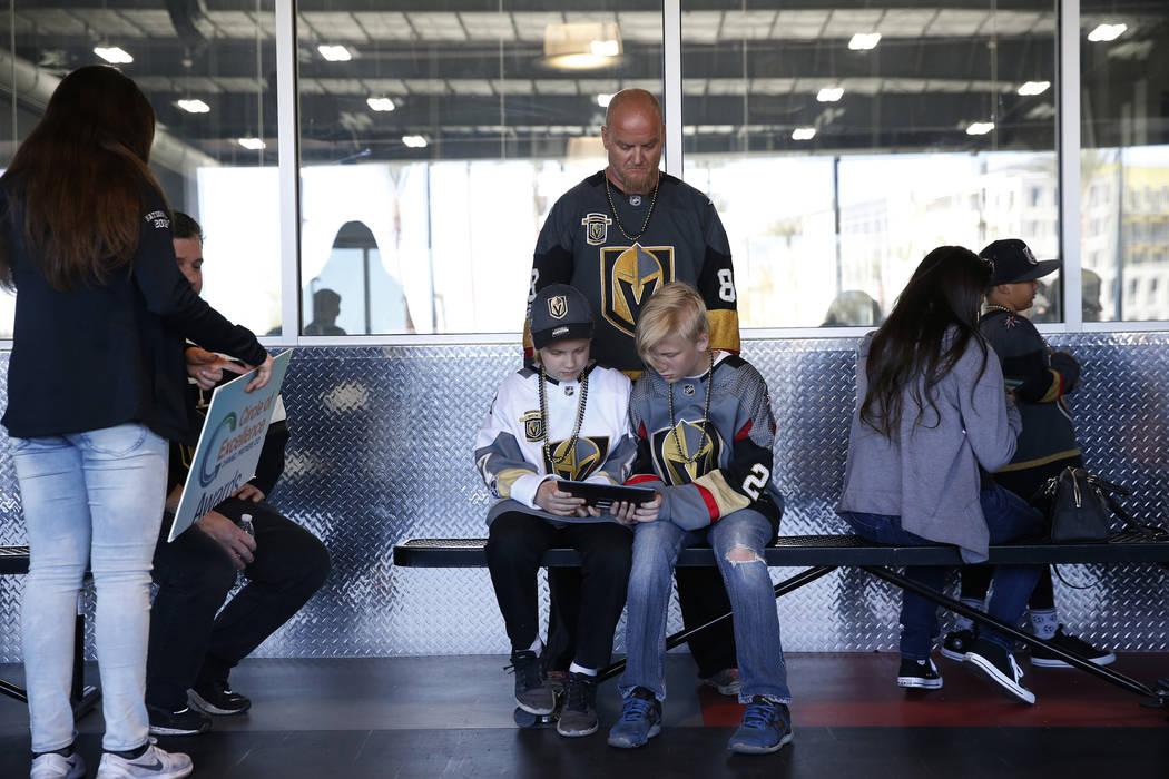 Brian Waldschmidt con sus hijos Caleb, 11, izquierda, y Jayden, 12, de Las Vegas, hacen cola para ingresar a la zona infantil durante una práctica Vegas Golden Knights en City National Arena en L ...