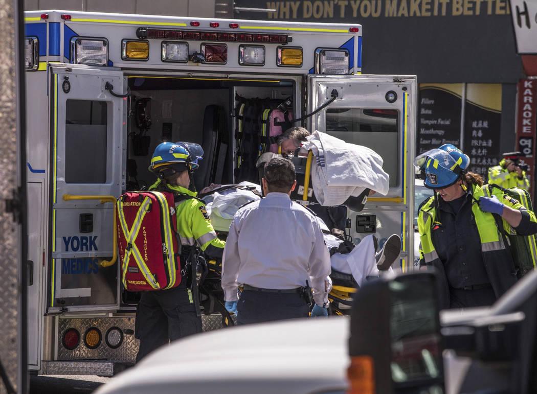 Una persona herida es ingresada en la parte trasera de una ambulancia en Toronto después de que una camioneta se estalló en una acera chocando contra una multitud de peatones el lunes 23 de abri ...