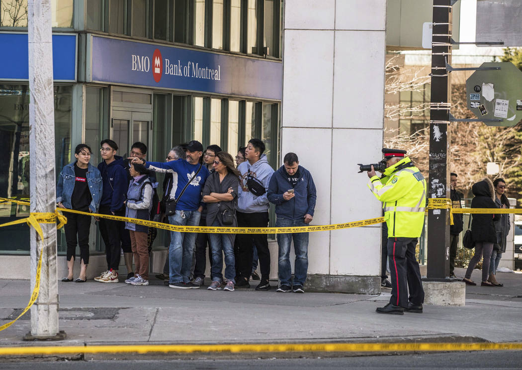 Un oficial de policía toma fotografías de la escena cuando los servicios de emergencia cierran la Calle Yonge en Toronto después de que una camioneta estalló en una acera chocando contra una m ...