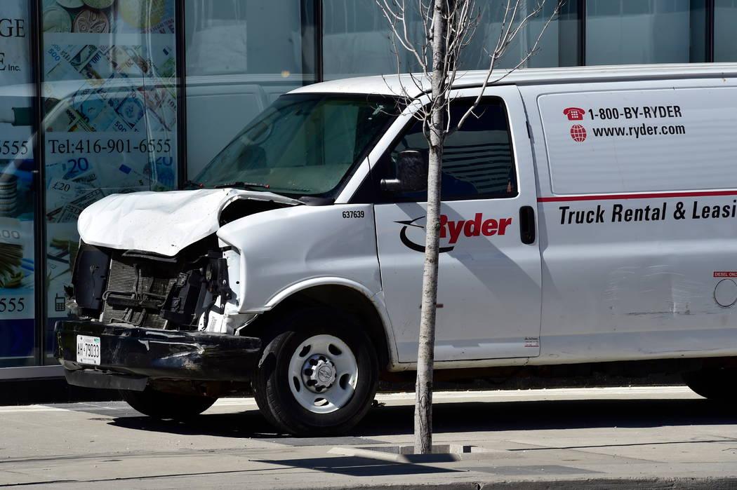 Una camioneta con una parte delantera dañada se encuentra inactiva en una acera después de que el conductor bajara por una acera chocando contra varios peatones en Toronto el lunes 23 de abril d ...