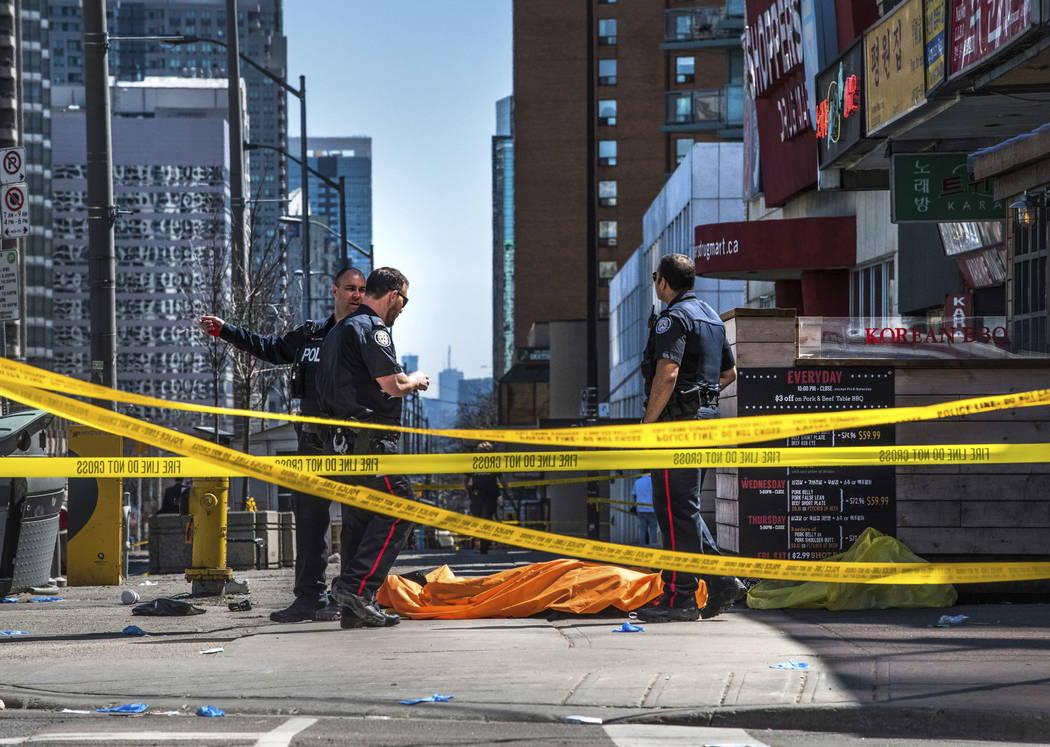 Agentes de la policía se paran junto a un cuerpo cubierto en Toronto después de que una camioneta se montó a una acera y se estrelló contra una multitud de peatones el lunes 23 de abril de 201 ...