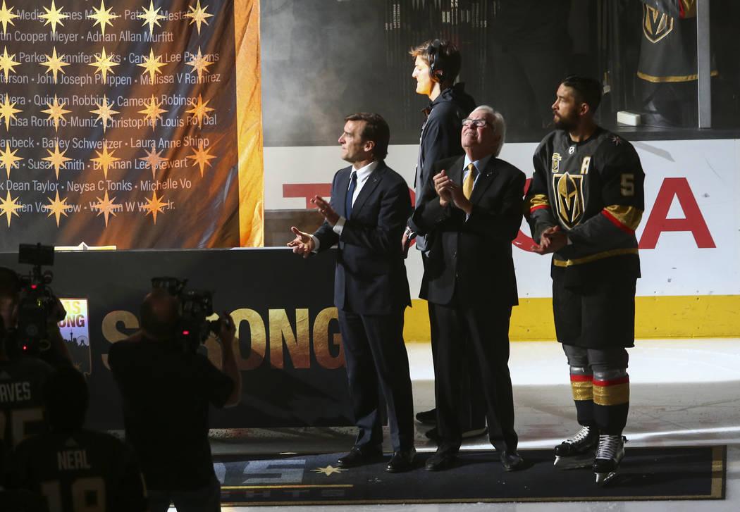 El gerente general de los Golden Knights, George McPhee, desde la izquierda, el propietario del equipo: Bill Foley y el defensa Deryk Engelland (5) miran mientras se alza una pancarta en honor a l ...