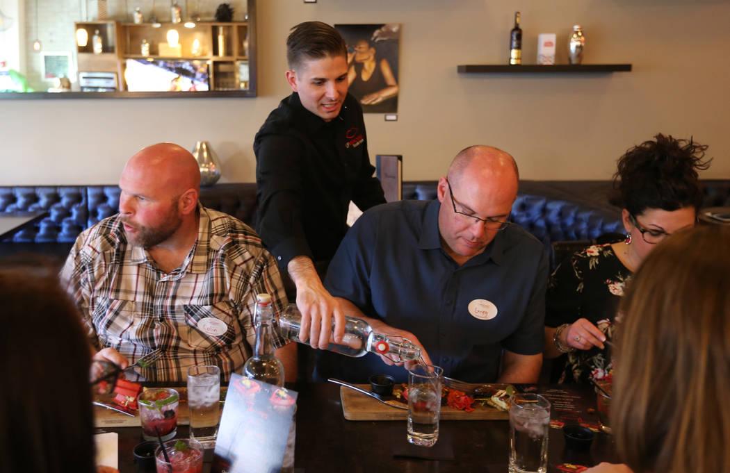 El presidente de Lip Smacking Foodie Tours: Donald Contursi, de pie, con Colin O'Neill, a la izquierda, y Greg O'Neill durante una parada de comida y bebida en Therapy, en el centro de Las Vegas, ...