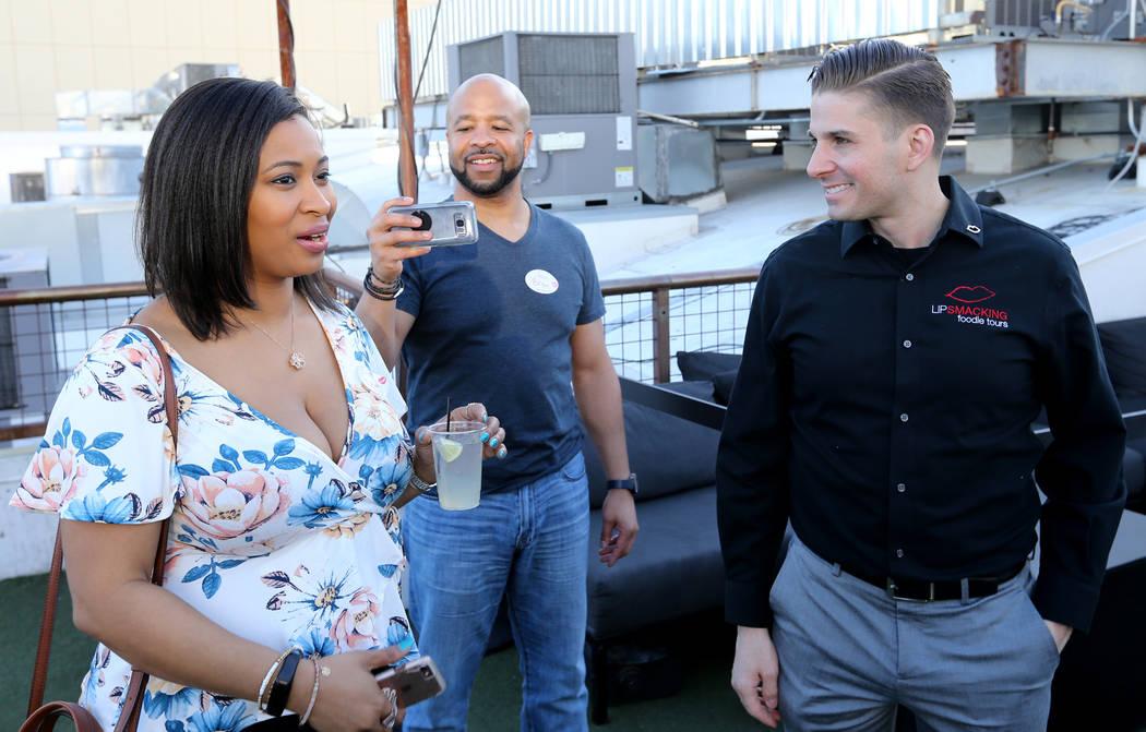 El presidente de Lip Smacking Foodie Tours: Donald Contursi, a la izquierda, con DeWana Williams, izquierda, y Bryon Wallington de Atlanta durante una parada de bebidas en el patio de la azotea en ...