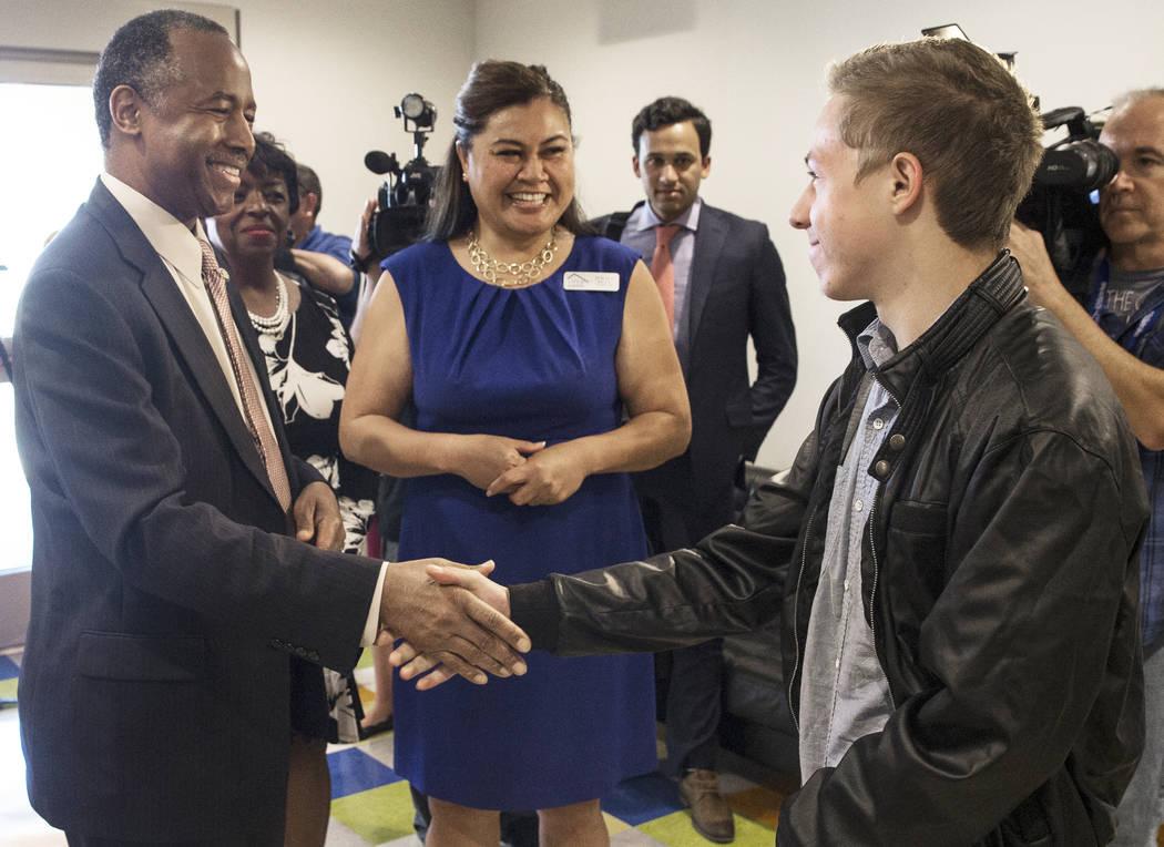 Ben Carson, izquierda, Secretario de Vivienda y Desarrollo Urbano, estrecha la mano del residente Daniel Sandoval-Collins durante una gira por el Shannon West Center for Homeless Youth el miércol ...