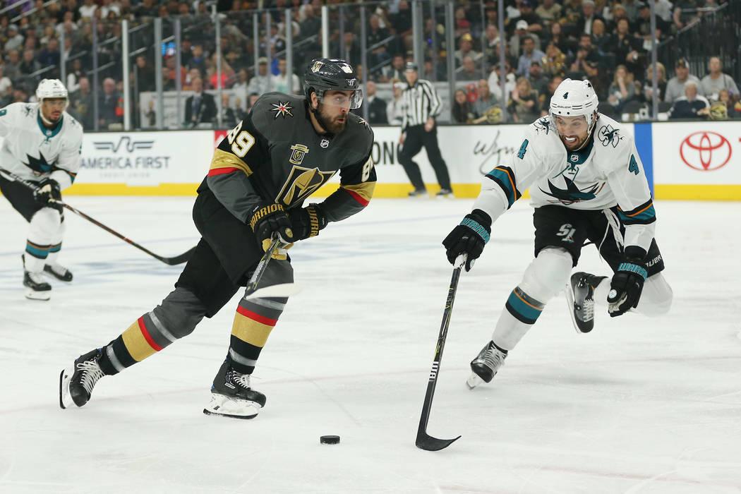 El ala derecha de Vegas Golden Knights: Alex Tuch (89) y el defensor de San José Sharks: Brenden Dillon (4) van por el disco durante el primer período en el 1er Juego de una serie de playoffs de ...