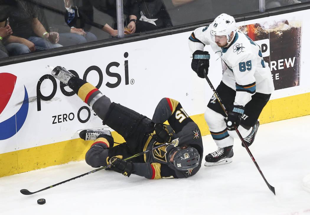 El defensor de los Golden Knights: Jon Merrill (15) se tropieza con el wing izquierdo de los San José Sharks: Mikkel Boedker (89) tras el disco durante el segundo periodo del 1er Juego de una ser ...