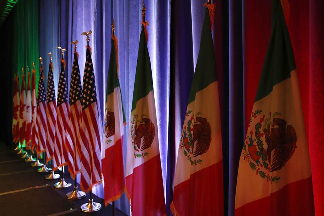 ARCHIVO.- Las banderas de Canadá, Estados Unidos y México en un escenario antes de una conferencia de prensa en Washington el 16 de agosto del 2017. Foto Jacquelyn Martin / AP.