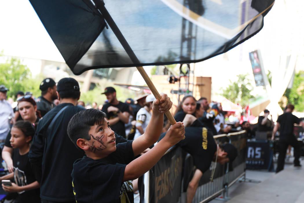 Daniel Arrieta, de 9 años, ondea una bandera durante una fiesta de Vegas Golden Knights para el sexto partido de los playoffs de la Stanley Cup en la Toshiba Plaza de Las Vegas el domingo 6 de ma ...