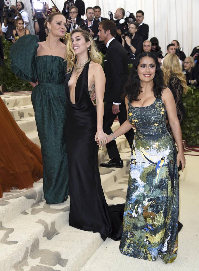 Stella McCartney, desde la izquierda, Miley Cyrus y Salma Hayek asisten a la gala del Costume Institute del Museo Metropolitano de Arte que celebra la apertura de la exposición Heavenly Bodies: F ...