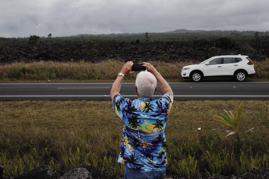 Roy Piper, quien visita desde Canterbury, Connecticut, toma fotografías mientras los gases volcánicos se emiten al aire el martes 8 de mayo de 2018 en Pahoa, Hawaii. Los funcionarios del condado ...